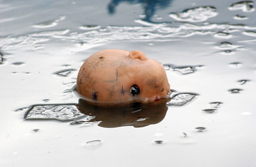 Scary doll head on a ice cold water, horror concept