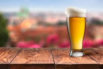 Glass of beer on wooden table against Prague