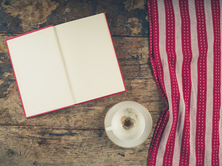 Empty coffee cup and open book