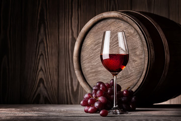 Red wine in glass and bunch of grapes
