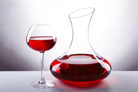 Glass carafe of wine on light background