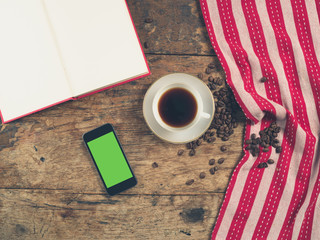 Coffee concept with cup, a book and a smart phone