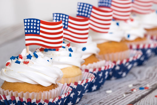 Row of patriotic cupcakes with sprinkles and American flags