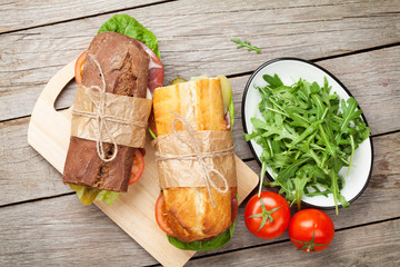 Two sandwiches with salad, ham, cheese and tomatoes