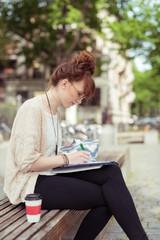 junge frau sitzt draußen auf einer bank und schreibt