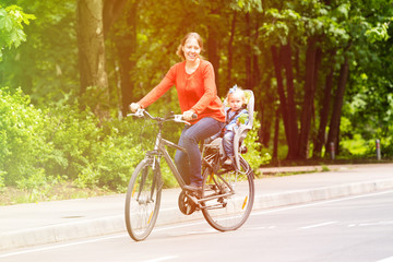 mother and little daughter on bike in summer