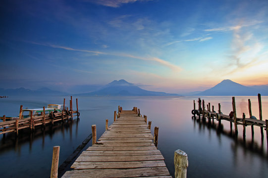 Colorful sunset at the Panajachel Pier with volcanoes in the background, Lake Atitlan, Guatemala, Central America