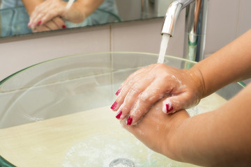 Hands washing with soap under running water