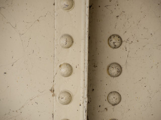 Painted metal rivets on the girders of a bridge are surrounded by old cobwebs.