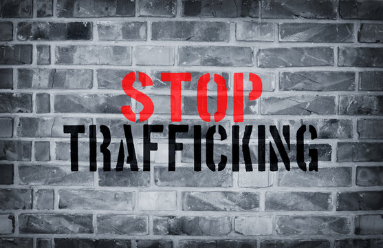 Stop Human trafficking stencil print on the grunge white brick w