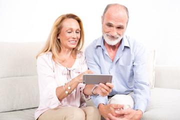 Glückliches älteres Ehepaar schaut auf ein Tablet