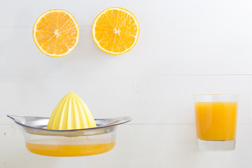 Halved orange with orange juice glass and squeezer with blank sp