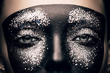 woman in black paint and glitter