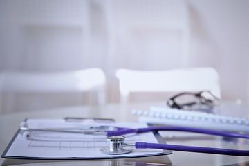 Purple stethoscope on the glass desk
