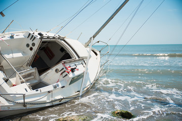 Tuinposter Schipbreuk sailboat wrecked and stranded on the beach