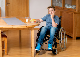 disabled boy in wheelchair is eating