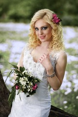 Beautiful young bride in white dress with bouquet in summer green park
