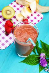 Smoothie mit Banane, Kiwi, Erdbeeren und Gartenkräutern