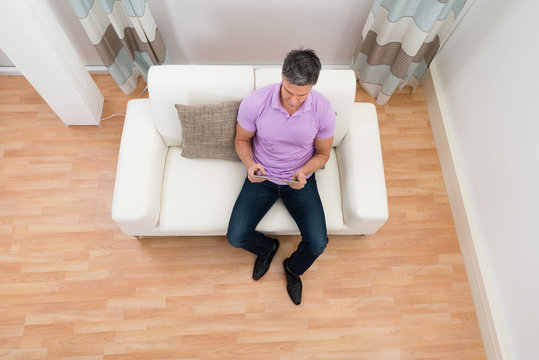 Man Sitting On Couch Using Digital Tablet