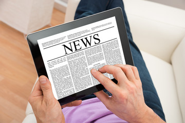 Man Reading News On Digital Tablet