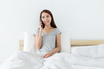 Woman talk to cellphone and sitting on bed
