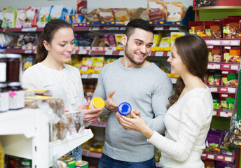 Cheerful adults choosing tinned food