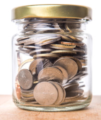 Malaysian coins in a mason jar over wooden background