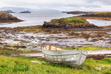Old fishing boat on Icelandic shore in summer.