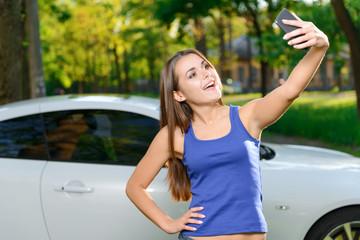Smiling girl doing selfie on background of car