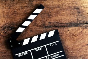 Movie clapper on old wooden background