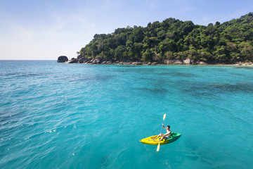 Young adult having fun with kayak in turquoise paradise sea