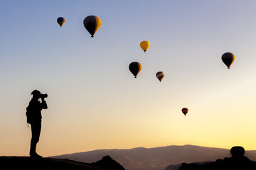 Tourist taking photos of hot air balloons in Cappadocia, Turkey
