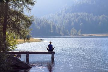 Woman doing yoga at lake