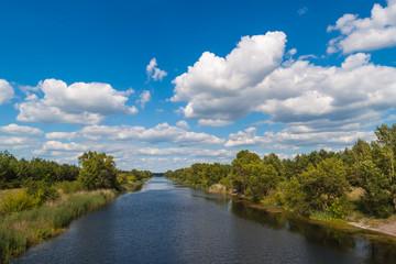 Landscape with white clouds above the river.
