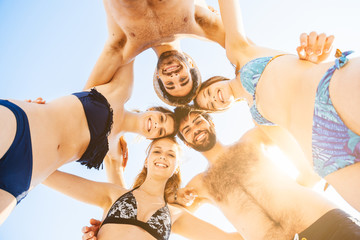 Group of friends embraced at the beach. View from below