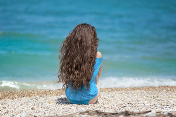 Long hair. Young attractive woman relax on the beach by blue wat