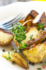 Baked new potatoes with herbs on a wooden background