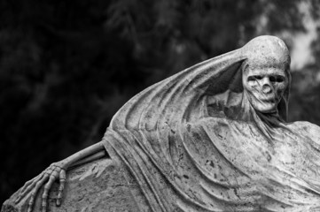 Beautiful, spooky cemetery sculpture depicting death.