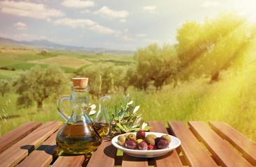 Olive oil and olives and on the wooden table against Tuscan land