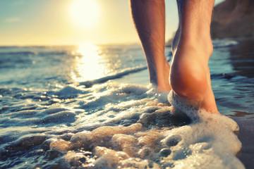 Wall Mural - Enjoying a barefooted walk at the ocean