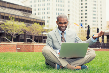 smiling man with laptop outdoor reading good news email