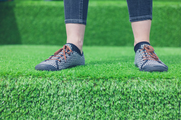 Feet of young woman standing on astro turf
