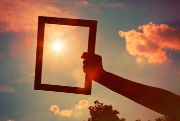 Hand holding a wooden frame on sunrise sky background. Care, saf