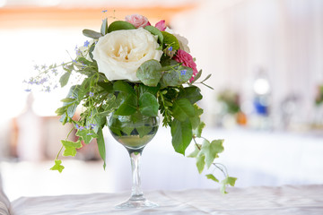 Flower arrangement of white roses and ivy is a crystal glass