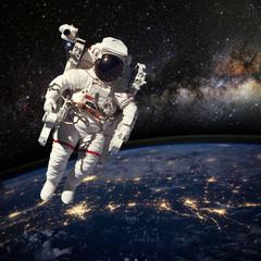 Astronauta w kosmosie nad ziemią w porze nocnej. Elem