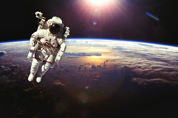 Astronaut in outer space above the earth during sunset. Elements
