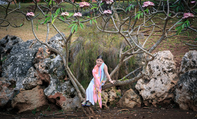 Fashionable styled looks like Bollywood  little girl sitting on tropical tree surrounded by a big natural rocks