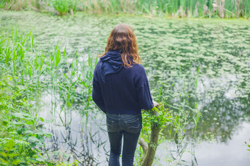 Young woman by pond in forest