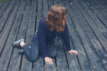 Young woman sitting on wooden deck