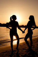 silhouettes of girlfriends  at sunset